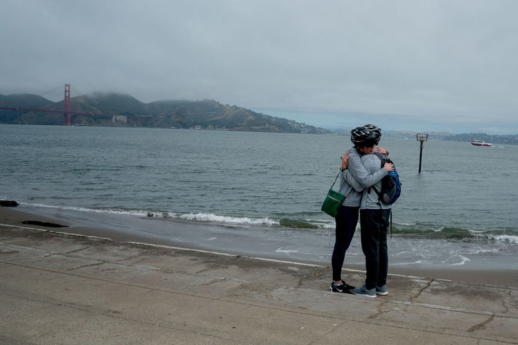 Lovers hugging each other infront of the famous golden gate bridge. Hugging Lovers Affection Affectionate Beauty In Nature Casual Clothing Cloud - Sky Couple,love, Day Full Length Leisure Activity Lifestyles Mountain Nature Outdoors Real People Scenics - Nature Sea Sky Standing Twinning Warm Clothing Water Women This Is Strength Holiday Moments Human Connection 2018 In One Photograph