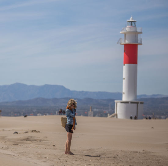 Full Length Of Woman Standing Against Lighthouse