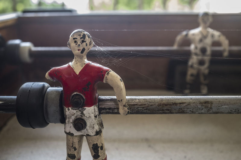 Close-up of old spider web on human representation in foosball table