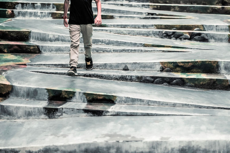 Low Section One Person Walking Staircase Wet Architecture Water Crossing Body Part Human Leg Day Crosswalk Road Human Body Part Road Marking Men Motion City Rain Outdoors Jeans