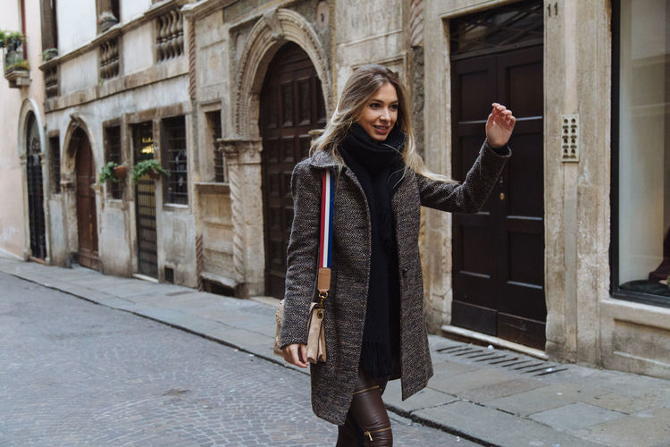 Smiling young woman walking in city