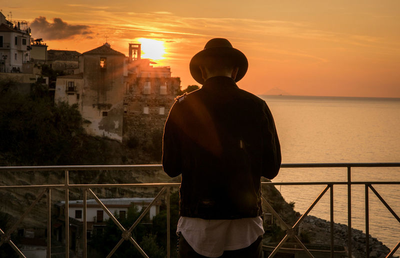 Rear View Of Silhouette Man Standing By Railing Against Sea During Sunset