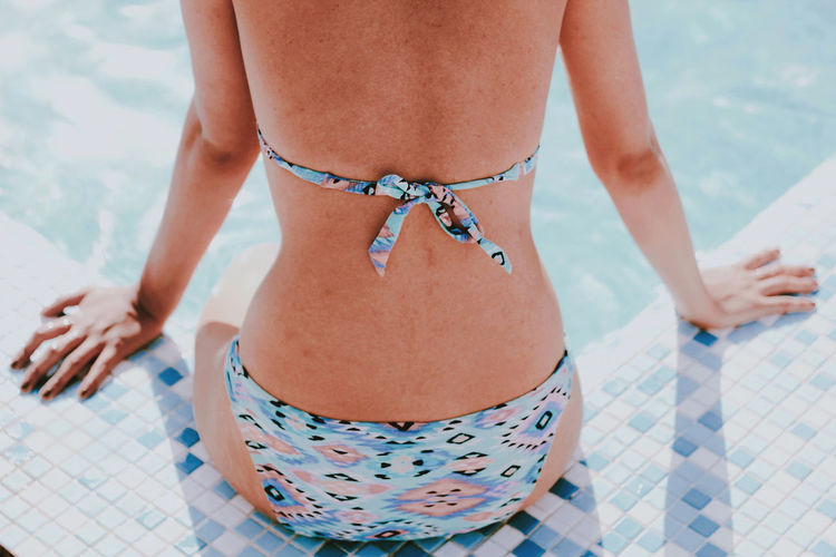 Midsection of woman in bikini swimming pool