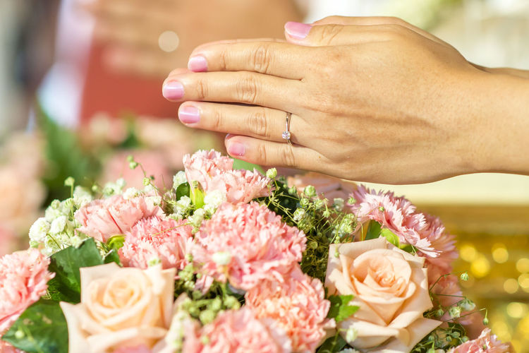 Cropped Hands Of Bridegroom Over Flowers During Wedding Ceremony