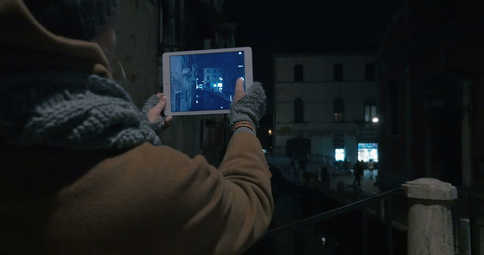 Rear view of man photographing illuminated smart phone at night