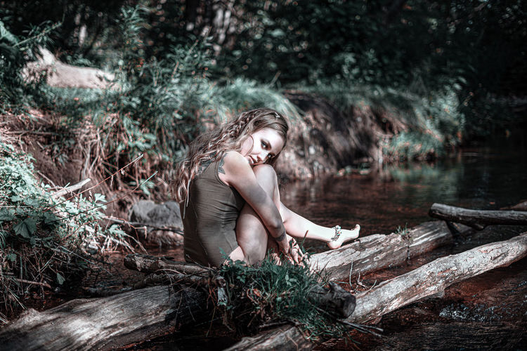 Young woman sitting on wood in forest