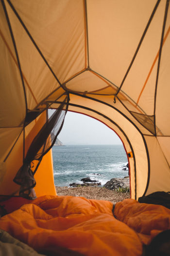 Scenic view of sea against sky seen through tent