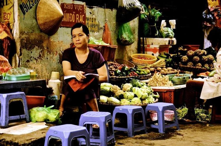 Reading the time away Streetphotography Street Life Street Peddler Street Photography Sitting Alone Sitting Empty Reading A Book Waiting Waiting For Customers Street Earning A Living Waiting For Waiting .... Bored Book Hanoi Hanoi Vietnam
