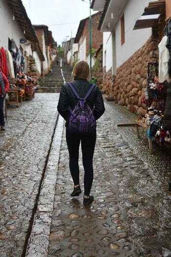 Full length rear view of woman walking on street
