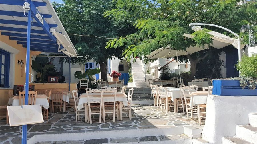 Empty chairs and tables in restaurant against buildings