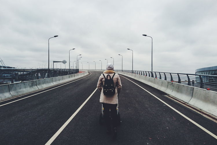 Rear View Of Woman Pushing Baby Stroller On Bridge Against Cloudy Sky