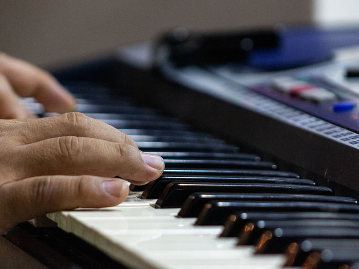 Cropped hands of person playing piano