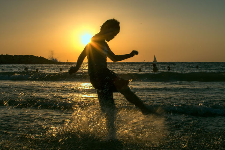 Boy kicking water in sea during sunset