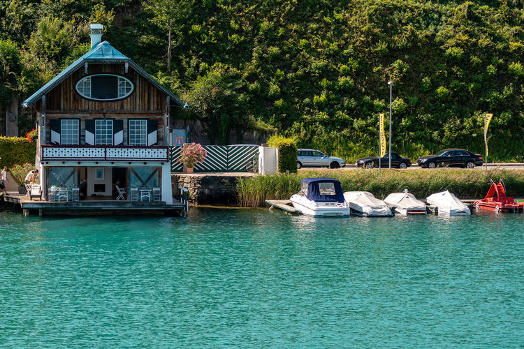 WORTHERSEE, AUSTRIA - AUGUST 08, 2018: Great scenery from the boat to the shore line of the lake, beautiful buildings, mountains, forests, highways. Tourists who enjoy a variety of water recreation types. Nature Day Outdoors Austria Carinthia Carinthian Lakes Tourist Tourists Lake Wörthersee Recreation  Leisure Landscape Water Sea Boats Motorboat Speedboats Summer People Holidays Fun Travel Beach Resort Lifestyle Sunny Rest Joy Waves Europe Alps Alpine Alpine Lake Tree Plant Built Structure Waterfront Nautical Vessel Transportation Architecture No People Green Color Building Exterior Mode Of Transportation River Tranquility Scenics - Nature Turquoise Colored