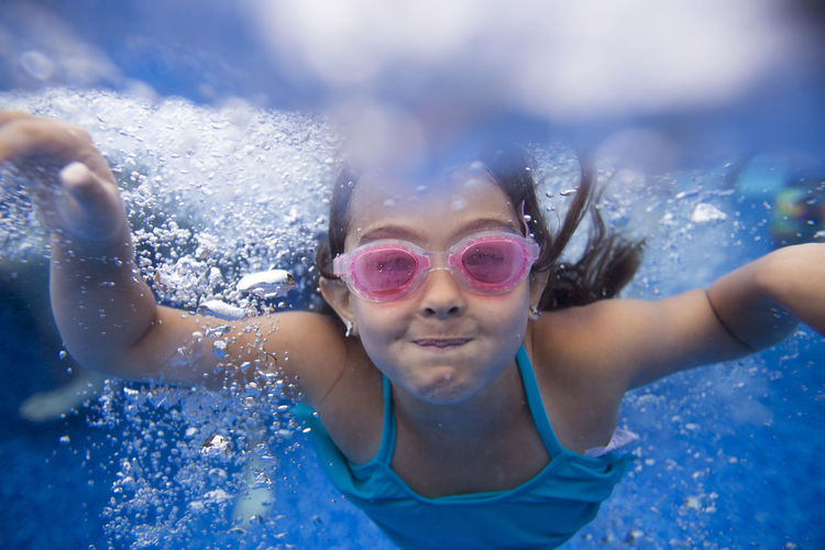 Close-Up Portrait Of Happy Girl Swimming In Water
