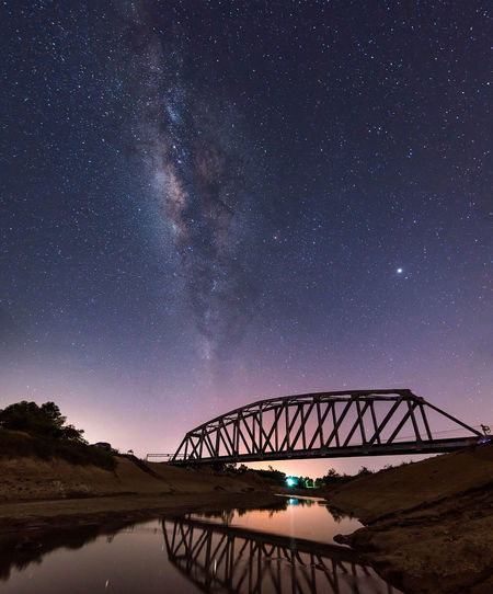 Scenic view of bridge against sky at night