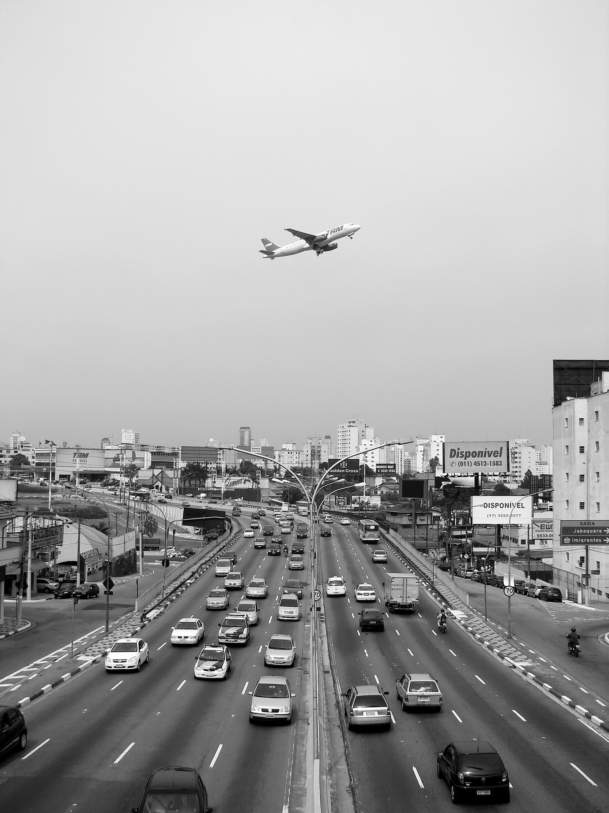 transportation, mode of transportation, motor vehicle, car, city, air vehicle, land vehicle, sky, road, motion, airplane, street, on the move, travel, no people, mid-air, day, nature, flying, traffic, cityscape