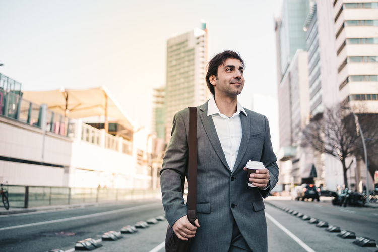 Businessman holding coffee cup standing on road