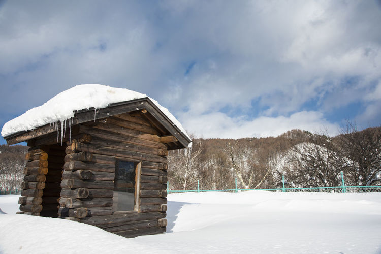 House on field against sky during winter