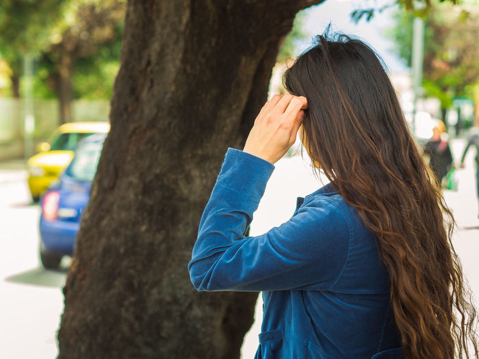 Rear view of woman by tree trunk