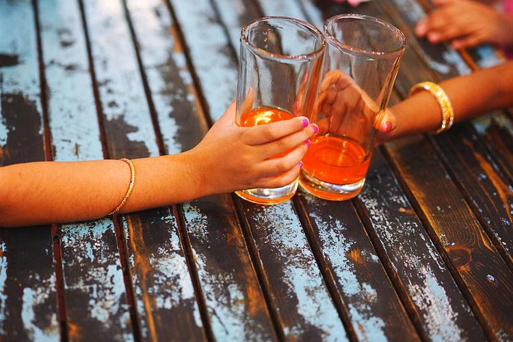 Cropped hands of girls holding glasses with drink on table