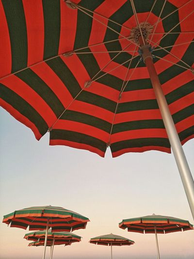 Low angle view of parasols against clear sky