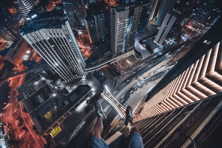 the man is sitting on the edge of the building with his legs hanging down The Architect - 2018 EyeEm Awards 17.62°