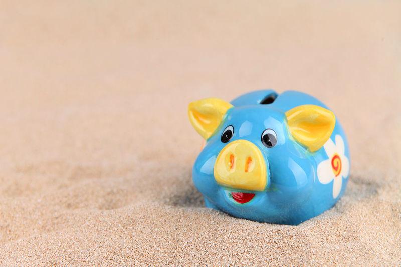 Close-up of piggy bank on sand