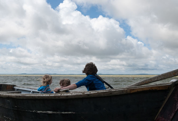 Children in rowboat against cloudy sky