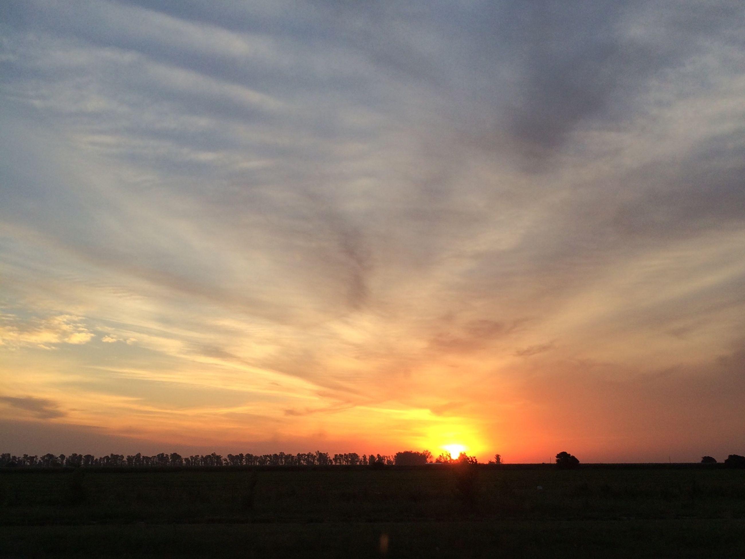 sunset, silhouette, sky, sun, orange color, tranquil scene, scenics, beauty in nature, tranquility, landscape, cloud - sky, nature, field, sunlight, idyllic, sunbeam, cloud, outdoors, no people, dramatic sky