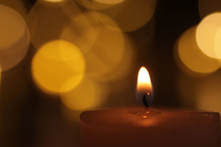 Close-up of lit candle in dark room with bokeh
