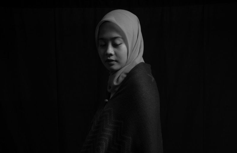 One Person Indoors  Black Background Portrait Headshot Lifestyles Standing Hood Looking Looking Down Clothing Young Adult Real People Studio Shot Copy Space Women Sadness Waist Up Dark Contemplation Hood - Clothing