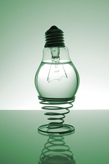 Upside down light bulb with liquid on coiled spring over table