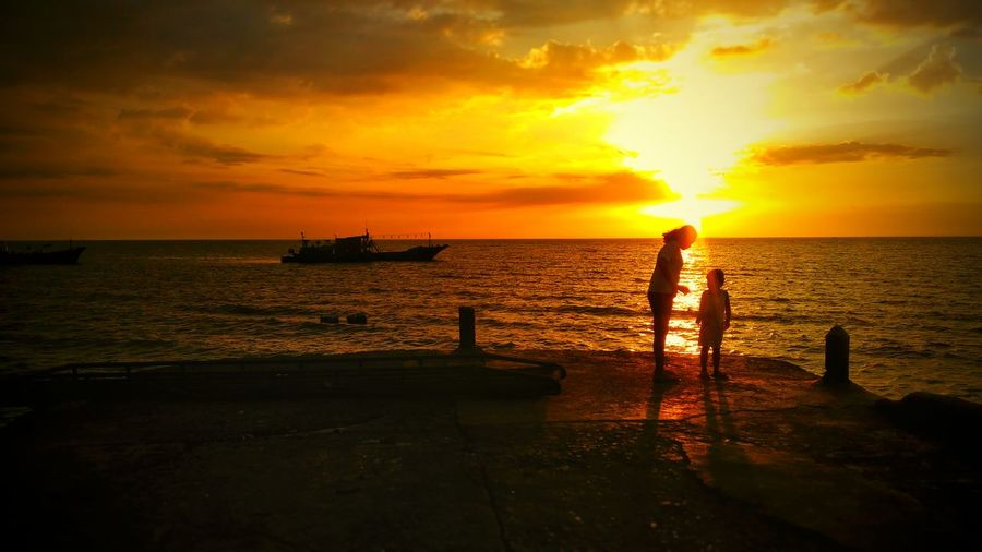 Woman and child on pier by sea against orange sky during sunset