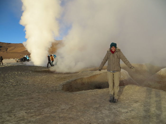 Portrait Of Happy Woman Standing Against Geyser Smoke
