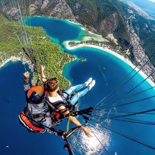 Extreme Sports Paragliding Parachute Flying Beach Water Nature Day Blue Sea Pool High Angle View Leisure Activity Real People Sunlight Outdoors Lifestyles Swimming Pool Reflection Motion