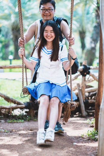 Full Length Leisure Activity Two People Looking At Camera Togetherness Portrait Emotion Front View Real People Smiling Women Playground Casual Clothing Swing Happiness Young Women Lifestyles People Young Adult Females Outdoors Rope Swing Positive Emotion