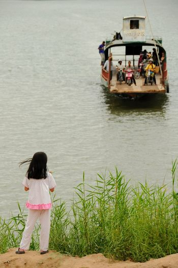 Rear view of girl looking at boat