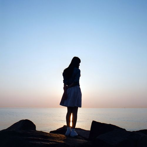 Full Length Of Woman Standing On Rock By Sea Against Sky During Sunset