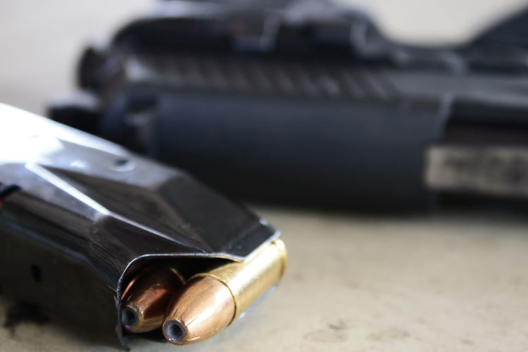 Close-up of magazine with bullets by gun on table