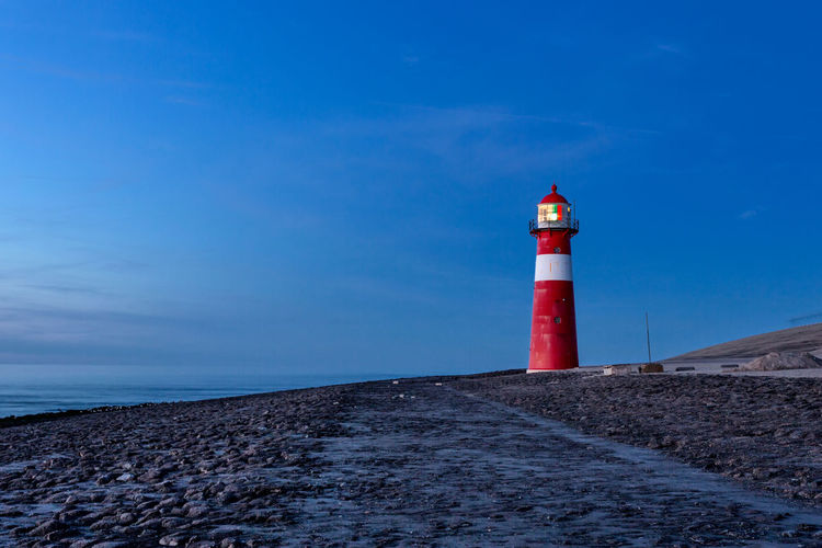 Lighthouse at sea shore against blue sky