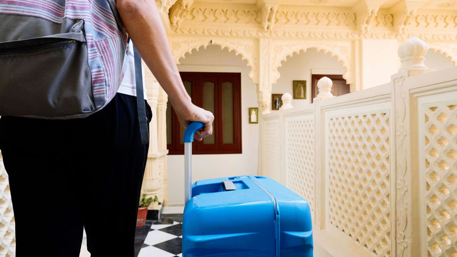 Midsection of woman carrying suitcase at hotel