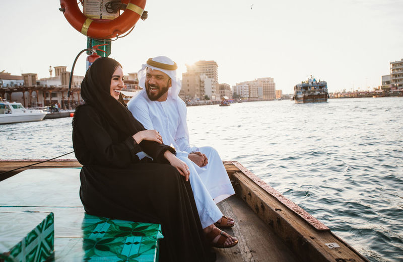 Cheerful couple talking while sitting in boat on river