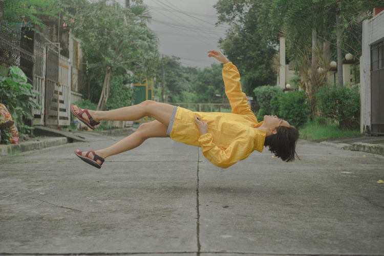 Side View Of Young Woman Levitating On Road