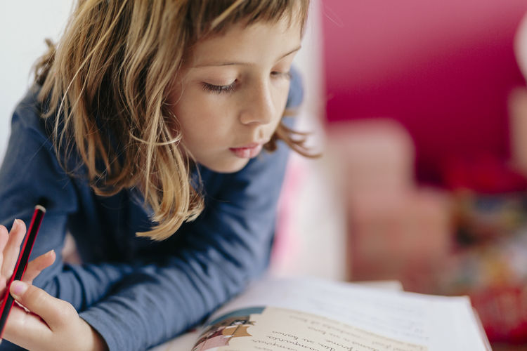 Girl looking away while holding book
