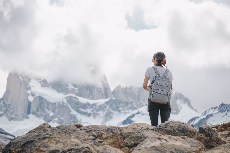 Rear view of woman standing on snowcapped mountain