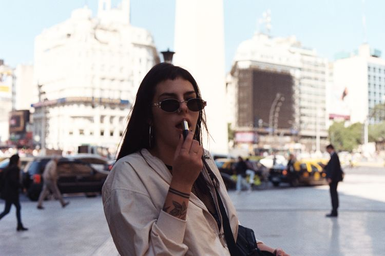 Young woman applying lipstick while standing in city