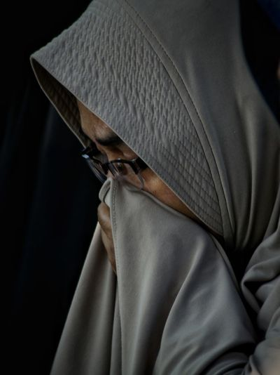 Close-up of mature woman in hijab against black background