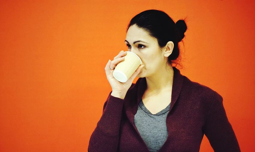 Woman holding disposable cup against orange background