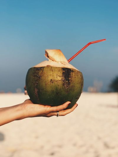 Close-up of hand holding fresh coconut against blue sky